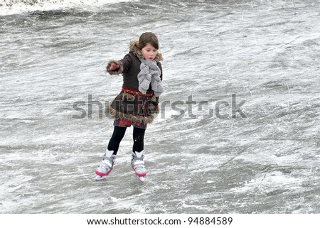 little girl learning ice skating outdoors - stock photo