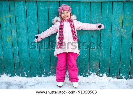 Little girl learning to skate at the rink near the house - stock photo