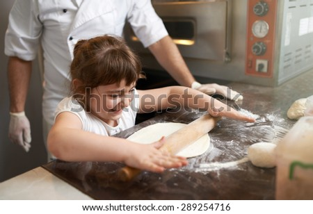 little girl learns to roll out the dough - stock photo