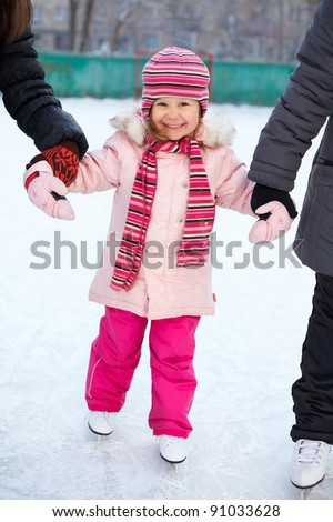 little girl learns to skate in the yard with older girlfriends - stock photo