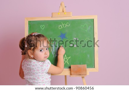 little girl learns to write with chalk - stock photo