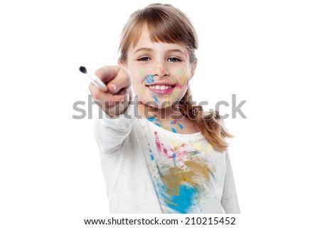 Little girl lending her paint brush to you - stock photo
