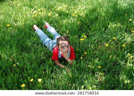 Little girl lies on a lawn with a blade of grass in a mouth. - stock photo