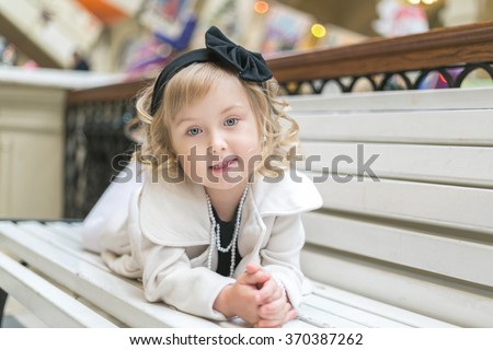 Little girl lies on a stylish bench and smiles. curly blond 4 years old with blue eyes - stock photo