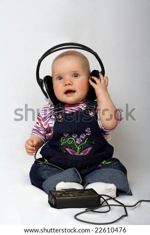little girl listen music in big headphones - stock photo