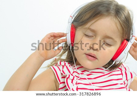 Little girl listening to music indoor. - stock photo