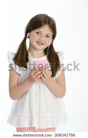 Little girl listening to music through headphones on a smartphone. She is smiling at the camera and standing against a white background.