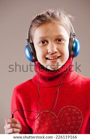 Little girl listening to the music inher blue headphones - stock photo
