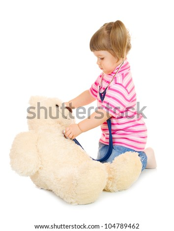 Little girl listens a stethoscope to a toy bear isolated