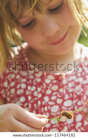 Little Girl Looking At Caterpillar On Blade Of Grass - stock photo