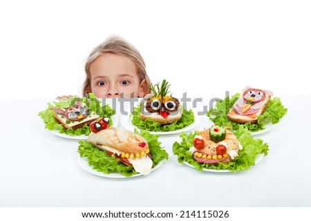 Little girl looking at creative food creatures - craving the party sandwiches, isolated - stock photo