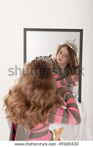 little girl looking at herself in mirror while playing make-up and fairy princess - stock photo