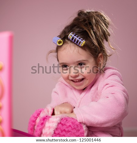 Little girl looking at mirror smiling - stock photo