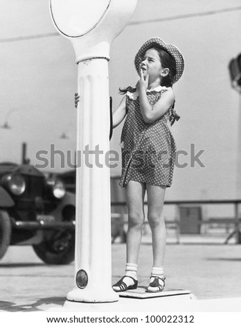 Little girl looking confused by a scale - stock photo