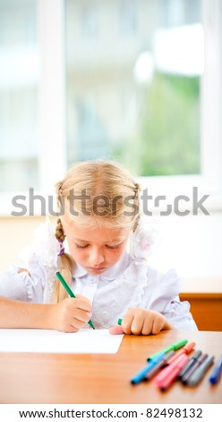 Little girl looking for a drawing concept wile painting picture on paper sheet. Indoors at classroom. Vertical Shot - stock photo