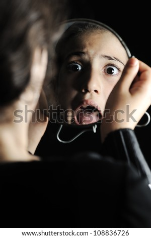 Little girl looking herself in the mirror - stock photo