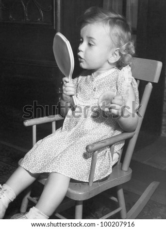 Little girl looking in mirror - stock photo