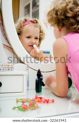 little girl looking in the bedroom mirror