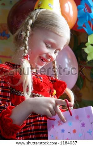Little girl looking inside her present bag - stock photo
