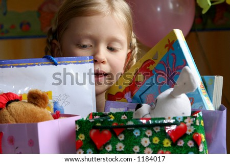 Little girl looking inside her present bags - stock photo