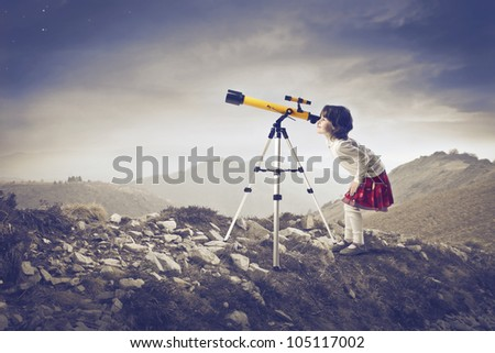 Little girl looking into a telescope in the mountains - stock photo