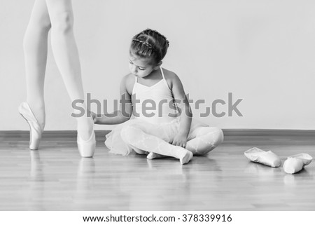 little girl looking on feet of trainer in ballet school