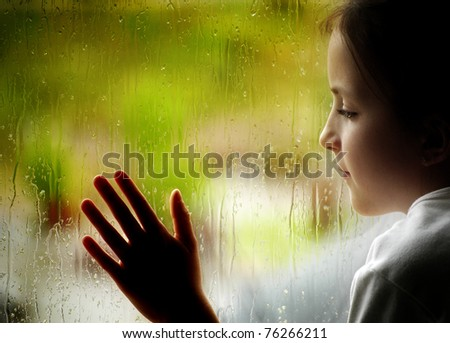 Little girl looking out window on a rainy day - stock photo
