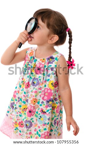 Little girl looking through a magnifying glass, isolated on white - stock photo