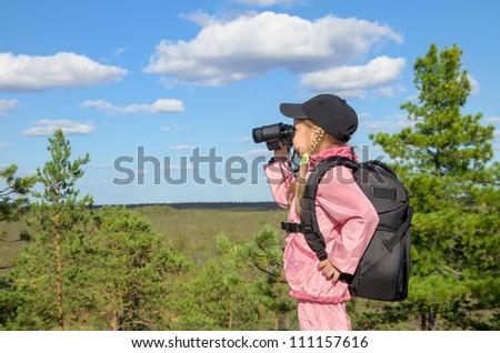 Little girl looking through binoculars from a high mountain - stock photo
