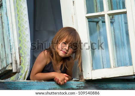 Little girl looks out the window rural house. - stock photo