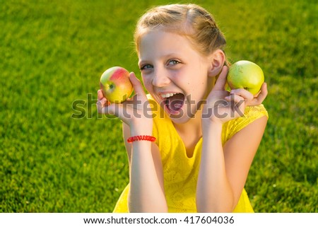Little girl loves apples as they are full of vitamines and are very tasty. Cheerful caucasian young lady is very artistic and likes to smile. Perfect retouching of a portrait. - stock photo