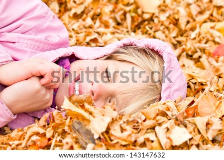 Little Girl Lying in Autumn Leaves with a big grin - stock photo