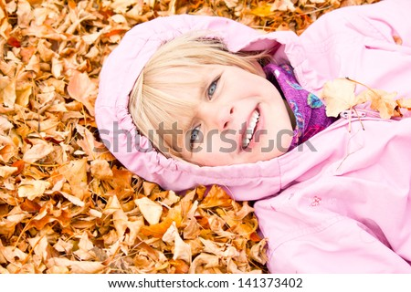 Little Girl Lying in Autumn Leaves with a big smile - stock photo