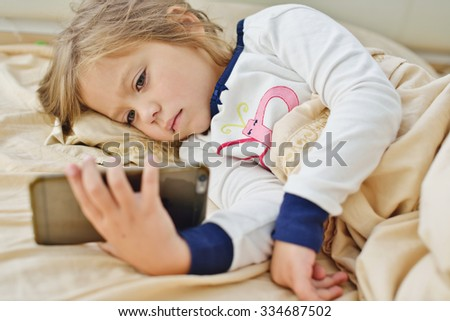 little girl lying in bed with smartphone at home