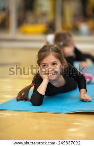 Little girl lying on a mat  in bodysuit, relaxing - stock photo