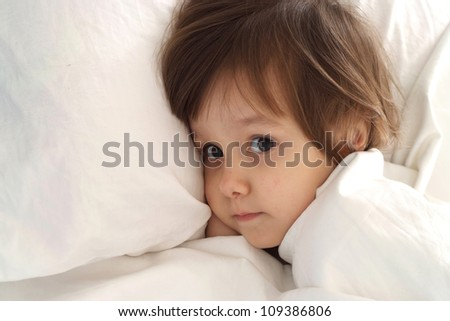 Little girl lying on bed at home