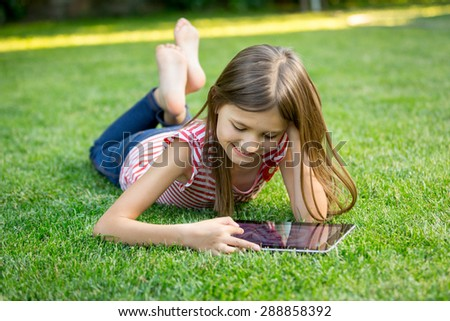 Little girl lying on grass and using tablet - stock photo
