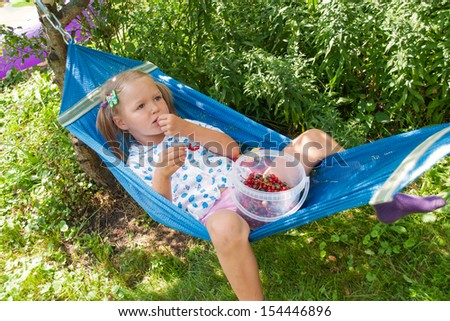 Little girl lying on hammock, eating berries and dreams