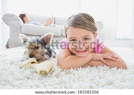 Little girl lying on rug with yorkshire terrier smiling at camera at home in the living room - stock photo