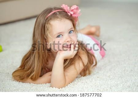 Little girl lying on the carpet - stock photo