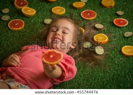 little girl lying on the grass with scattered fruit, grapefruit, orange, lime - stock photo
