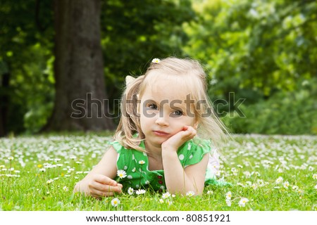 Little girl lying on the green grass with flowers - stock photo