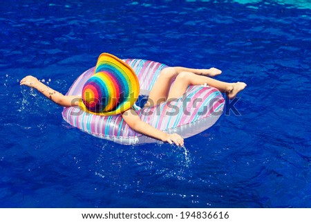 little girl  lying on the  inflatable rubber circle  in the swimming pool