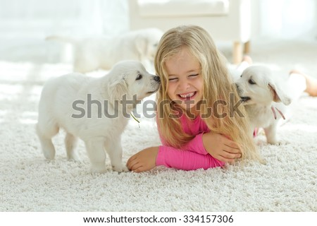 Little girl lying on the mat with labrador, smiling at camera at home in the living room - stock photo