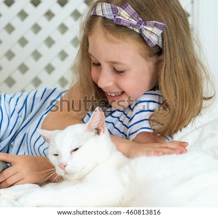 Little girl lying with cat on the bed.v