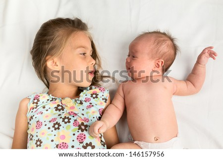 Little girl lying with her newborn sister on a white blanket - stock photo
