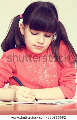 Little girl makes the lessons written on the background pile of old books. - stock photo