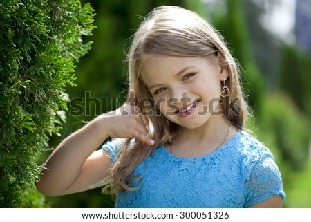 Little Girl making a call me gesture, against background of summer park - stock photo