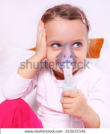 Little girl making aerosol treatment with a rubber masks