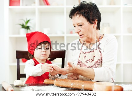 Little girl making dough in the kitchen with grandma - stock photo
